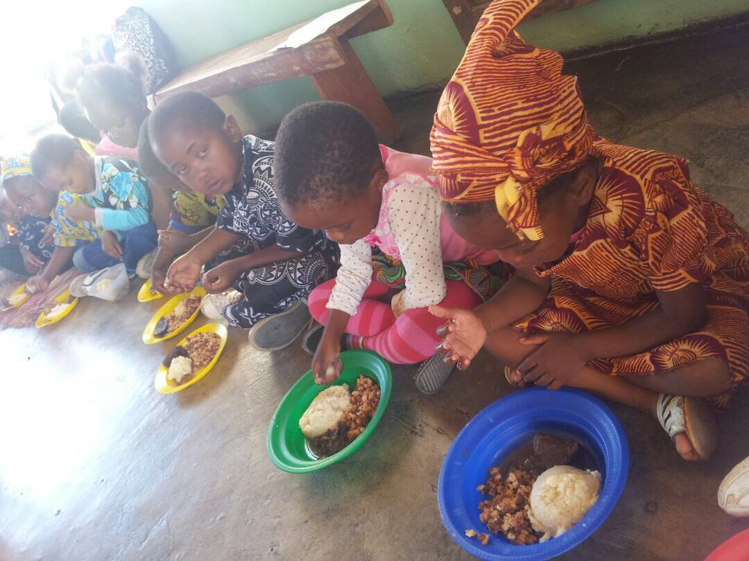The children enjoying a special meal of beans, sadza and cabbage.